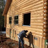 Grizzly III builder constructing log siding