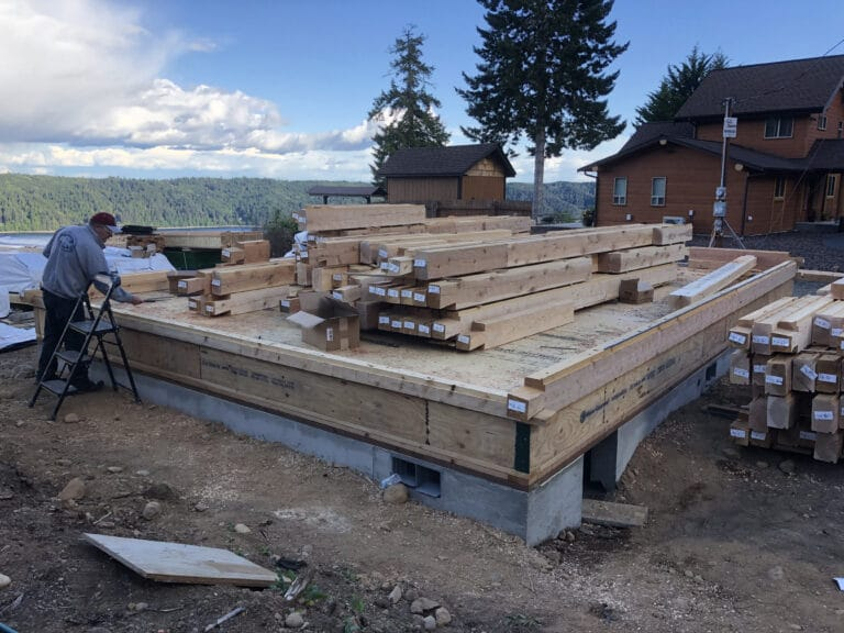 Hood Canal WA cozy log cabin home construction with scenic tree line and water